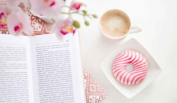 a book cup of coffee and flavoured donut on square white ceramic bowl